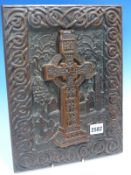 AN IRISH CARVED OAK PANEL DEPICTING A CELTIC CROSS IN THE GRAVE YARD OF A RUINED CHURCH FRAMED BY