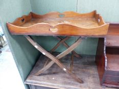 A MAHOGANY BUTLER'S TRAY WITH SHAPED GALLERY SIDES, ON A FOLDING STAND. 76 x 45cms.