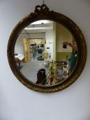 AN ROUND MIRROR IN GILT FRAME CRESTED BY RIBBON TIED FRONDS.
