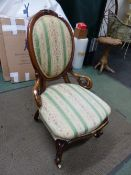 A VICTORIAN CARVED WALNUT OVAL BACK LADIES CHAIR, CERAMIC CASTERS.