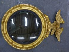 A CONVEX MIRROR WITHIN REEDED SLIP AND BEADED GILT FRAME SURMOUNTED BY AN EAGLE. H 90 x Dia. 63cms.