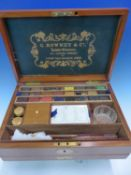A ROWNEY MAHOGANY PAINT BOX COMPLETE WITH CAKES OF PAINT, TWO PALETTES, GLASS WATER BOWL, BRUSHES