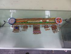 AN ISLAMIC BEADED TEXTILE BELT SEWN WITH 1990S TURKISH COINS AND HUNG WITH COLOURED PASTE MOUNTED