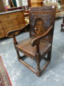 AN ANTIQUE.COUNTRY OAK WAINSCOT CHAIR WITH CARVED PANEL BACK.