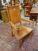 AN UNUSUAL VICTORIAN GOTHIC OAK ARMCHAIR ON OCTAGONAL TAPERED LEGS.