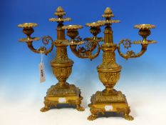 A PAIR OF ORMOLU TWO BRANCH CANDLEABRA, THE ARMS SCROLLING EITHER SIDES OF CENTRAL VASES ON SQUARE