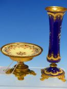 A FLORAL ENAMELLED ROYAL BLUE GROUND WAISTED CYLINDRICAL VASE ON FOUR ORMOLU FEET. H 15cms. ROGETHER