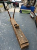 A MASSIVE WOODEN PLANE WITH TWO BLADES AND TWO SPOKE HANDLES TO ONE END. W 150cms.