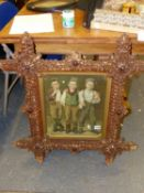 A VINTAGE TRAMP ART TYPE CORK FRAME ENCLOSING AN IMAGE OF THREE BOYS. 80 x 74cms. TOGETHER WITH AN