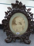 A VICTORIAN CARVED BLACK FOREST OVAL EASEL, BACK FRAME DECORATED WITH LEAVES AND FLOWERS. CONTAINING