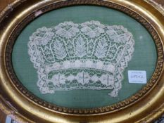 AN ANTIQUE WHITE LACEWORK CRAVAT WITH FLOWER AND FRUIT DECORATION NOW FRAMED TOGETHER WITH AN OVAL