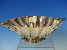 A WHITE METAL FLUTED LEAF FORM FOOTED BOWL WITH SCROLL HANDLES. ENGRAVED WITH ARMORIAL CRESTS. W.