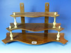 AN UNUSUAL VICTORIAN MAHOGANY THREE TIER HANGING WALL SHELF WITH TURNED BONE SUPPORTS. W. 46 x H.