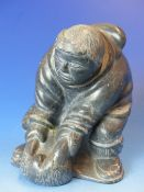 AN INUIT CARVED LIMESTONE FIGURE OF A HUNTER, BASE INSCRIBED. H. 16cms.