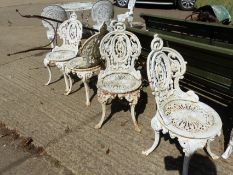 A SET OF FOUR CAST IRON VICTORIAN STYLE GARDEN CHAIRS.