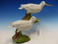 A PAIR OF MAJOLICA WHITE WADING BIRDS WITH LONG YELLOW BEAKS, THEIR RED LEGS ON GREEN FOLIAGE