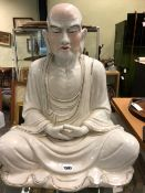 A CHINESE FIGURE OF A MEDITATING MONK SEATED CROSS LEGGED AND WITH HIS HANDS CLASPED IN THE LAP OF