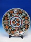 A JAPANESE IMARI DISH, THE ALTERNATING ROUNDELS AND FAN SHAPES ON A PEONY GROUND ENCLOSING THE