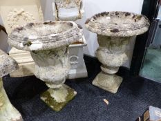 A PAIR OF RECONSTITUTED STONE GARDEN URNS DECORATED WITH CLASSICAL FIGURES.