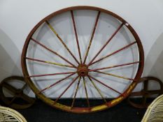 A PAIR OF LARGE IRON CARTWHEELS AND FOUR SMALLER IRON RAIL WHEELS.