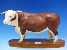 A BESWICK CONNOISSEUR MODEL HEREFORD BULL STANDING ON AN ELONGATED OVAL WOODEN BASE. W29cms.