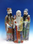 THREE FIGURES OF THE SHULUFU TRIAD, THEIR ROBES PAINTED IN FAMILLE ROSE ENAMELS, SHOULAO WITH