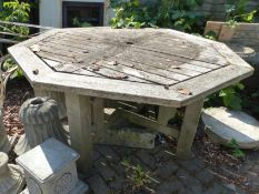 A LARGE OCTAGONAL TEAK GARDEN TABLE AND SIX CHAIRS TOGETHER WITH A SMALLER GARDEN TABLE.