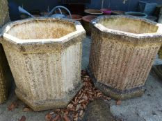 A PAIR OF OCTAGONAL COMPOSITE STONE TERRACE PLANTERS WITH FLUTED SIDES, H 52cms.
