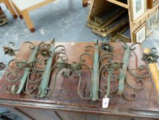 A SET OF FOUR WROUGHT IRON WALL MOUNTED TWO BRANCH CANDLE SCONCES. (4)