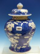 A CHINESE BLUE AND WHITE BALUSTER JAR AND COVER PAINTED WITH WHITE CHERRY BLOSSOMS AGAINST A BLUE