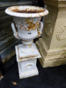 A PAIR OF VICTORIAN STYLE SMALL CAST IRON URNS ON PEDESTAL BASES AND A PAIR OF ROCOCO STYLE IRON