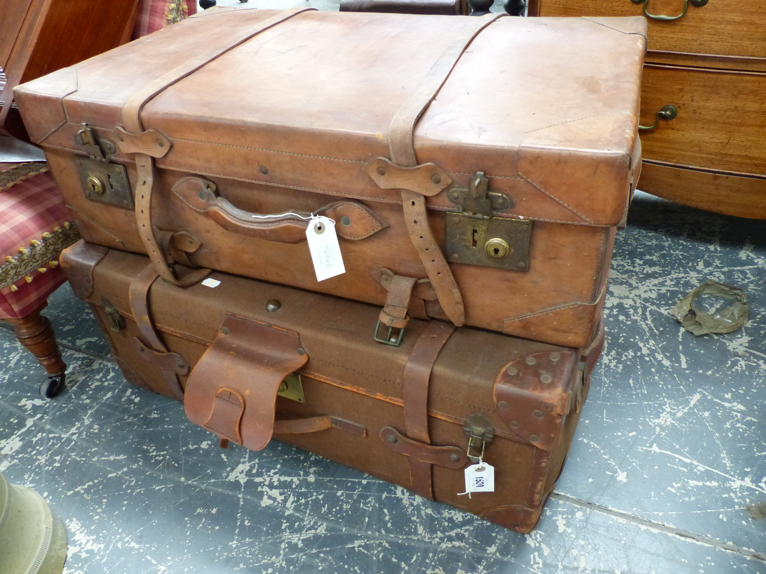 Lot 1560 - A LARGE VINTAGE LEATHER SUITCASE AND A SIMILAR LEATHER MOUNTED CANVAS EXAMPLE. (2)