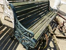 AN ANTIQUE GREEN PAINTED GARDEN BENCH WITH CAST IRON ENDS.