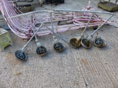 A SET OF SIX VINTAGE CAST IRON CATTLE FEEDERS.