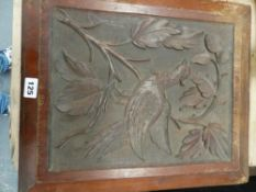 A CARVED WOODEN PANEL.