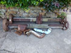 A PAIR OF VINTAGE AXLES, RAIN HOPPERS AND A WALL MOUNTED IRON HORSE HEAD.