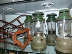 FOUR TILLY LAMPS AND TWO SADDLE RACKS.