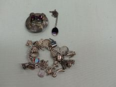 A SILVER CHARM BRACELET, A SILVER SCOTTISH THISTLE BROOCH, AND A BLUE JOHN SILVER CASED PENDANT.
