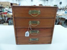A FOUR DRAWER WOODED JEWELLERY CASE AND CONTENTS COMPRISING OF MAINLY COSTUME JEWELLERY.