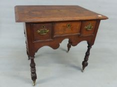 AN 18th.C. AND LATER OAK LOWBOY WITH THREE DRAWERS TO DECORATIVE SHAPED FRIEZE STANDING ON TURNED