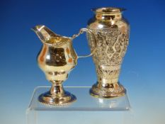 SILVER HELMET JUG MARKS WORN, AND A 900 GRADE EASTERN SILVER REPOUSSE ENGRAVED VASE. HEIGHT 13.5cms.