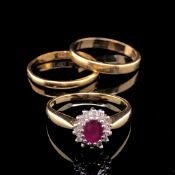 AN 18ct GOLD RUBY AND DIAMOND OVAL CLUSTER RING, FINGER SIZE K, TOGETHER WITH AN 18ct GOLD WEDDING