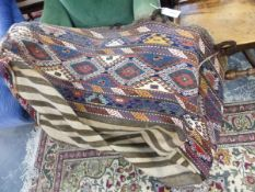 AN ANTIQUE CAUCASIAN FLAT WEAVE CRADLE. L. 100 x H. 42cms.
