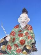 A JAPANESE PORCELAIN FIGURE OF A SEATED ELDERLY DIGNITARY, HIS GREEN ROBE WITH IRON RED ROUNDELS