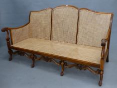 AN EARLY 20th.C. BERGERE CANE BACK THREE SEAT SOFA ON CARVED CAROLEAN STYLE LEGS AND STRETCHER,