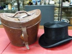 A RED SILK LINED LEATHER TOP HAT CASE CONTAINING A MOSS BROS. TOP HAT WITH BLACK SILK PILE, THE