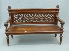 A VICTORIAN OAK SETTLE, THE BACK PIERCED WITH ANTHEMION MOTIFS, THE FOLIATE CARVED HANDLES TO THE
