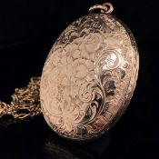 A 9ct GOLD SCROLL ENGRAVED OVAL LOCKET SUSPENDED ON A 9ct GOLD FIGARO STYLE CHAIN. LOCKET