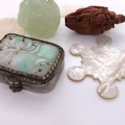 TWO CHINESE MOTHER OF PEARL COUNTERS, A STAR SHAPED SILK SPOOL, A COQUILLA NUT MONKEY RIDING A