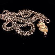 A VICTORIAN 9ct OLD GOLD UNHALLMARKED, FANCY LINK GRADUATED ALBERT CHAIN WITH A HANGING CHIMPANZEE